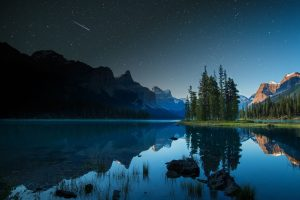 A shooting star goes over Spirit Island on Maligne Lake in Jasper, Alberta, Canada.